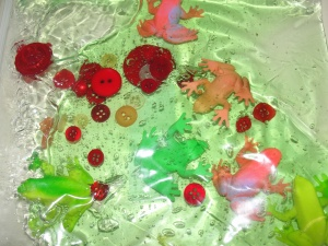 simple sensory ziplocking bag filled with green goop various red buttons and frog figurines