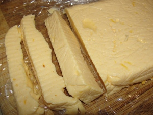 velveeta style american cheese shown sliced and on a syran wrapped cutting board