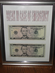 Two five dollar bills in a glass picture frame that says break in case of emergency