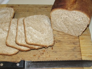 4 Sons 'R' Us: Honey Wheat Sandwich Bread half a loaf shown sliced on a brown wooden cutting board