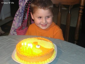 Lorax Party - child shown with Lorax themed with lit candles, seated at the table
