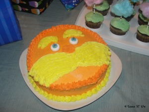 Lorax Party cake with the lorax face made from buttercream frosting on a white plate