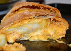 Buffalo Chicken Bake is shown sliced on a dark baking sheet pan with melted cheese oozing out