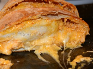 Buffalo Chicken Bake sliced open on a dark baking sheet pan with melted cheese oozing out