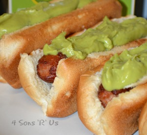 Bacon Wrapped California Dogs shown topped with creamy green avocado on a white serving plate