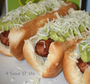 Bacon Wrapped California Dogs topped with creamy avocado & shredded monterrey jack cheese on a white plate