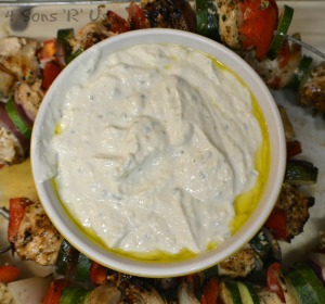 Grilled Greek Chicken Kabobs surrounding tzatziki sauce with olive oil in a large white bowl all set on a cutting board